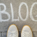 View from above, female feet with text blog written on grey sidewalk